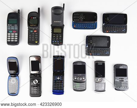 IRVINE, CALIFORNIA, SEPT 15, 2019: A large group of outdated cell phones frov different manufacturers and providers, on white.