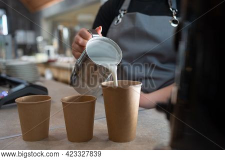 Barista Woman Pours Milk Into Glasses With Coffee From A Metal Jug. Paper Cups With Coffee And Milk.