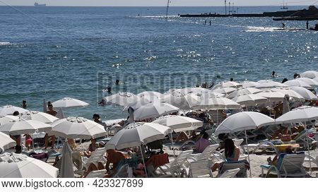 Sea View With White Sun Umbrellas At Luxury Beach Resort. Sun Tanning People Rest On Lounge Chairs I