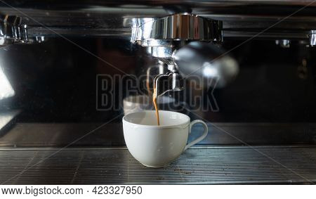 Coffee Is Poured Into A White Ceramic Cup From The Coffee Machine. The Process Of Making Coffee In A