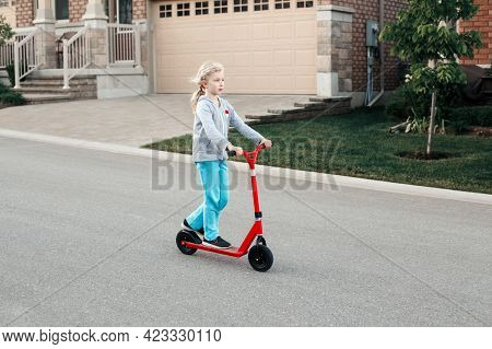 Young Girl Child Riding Red Scooter On Street Road Park Outdoor. Summer Fun Eco Sport Activity Hobby