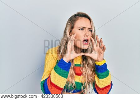 Beautiful young blonde woman wearing colored sweater shouting angry out loud with hands over mouth