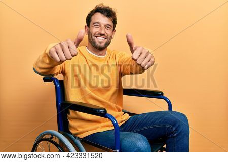 Handsome man with beard sitting on wheelchair approving doing positive gesture with hand, thumbs up smiling and happy for success. winner gesture.