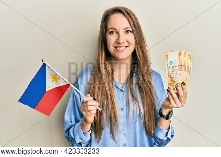 Young blonde woman holding philippine flag and philippines pesos banknotes smiling with a happy and cool smile on face. showing teeth.