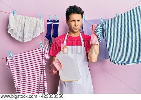 Handsome hispanic man doing laundry holding detergent bottle annoyed and frustrated shouting with anger, yelling crazy with anger and hand raised