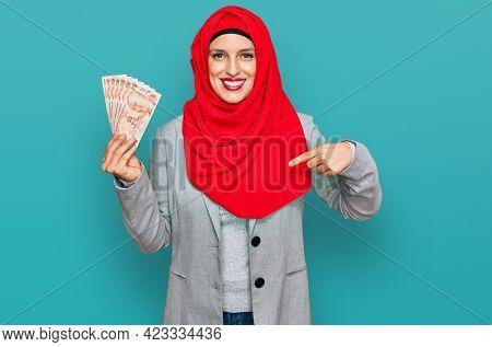 Beautiful hispanic woman wearing islamic hijab holding turkish lira banknotes pointing finger to one self smiling happy and proud