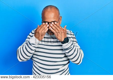Middle age latin man wearing casual clothes and glasses rubbing eyes for fatigue and headache, sleepy and tired expression. vision problem