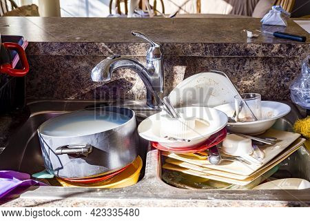 Close Up Frontal View Of A Kitchen Mess With Dirty Pots, Dishes And Utensils Have Piled Up In Kitche