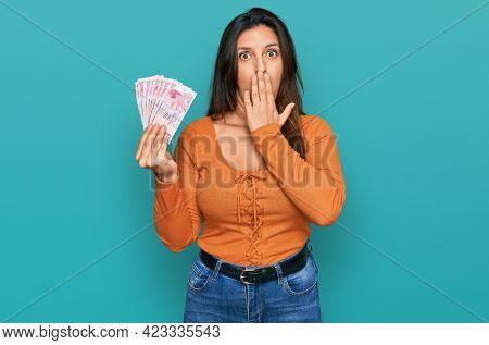 Beautiful hispanic woman holding 50 turkish lira banknotes covering mouth with hand, shocked and afraid for mistake. surprised expression