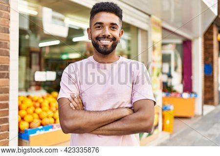 Hispanic man standing by fruits and vegetables shop. Smiling happy with crossed arms by marketplace