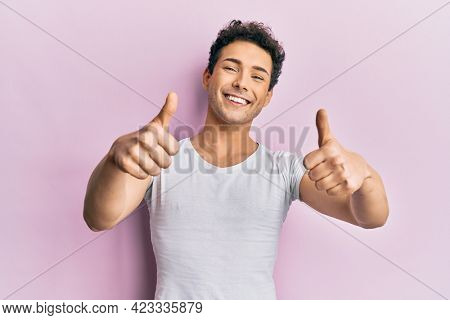 Young handsome man wearing casual white t shirt approving doing positive gesture with hand, thumbs up smiling and happy for success. winner gesture.