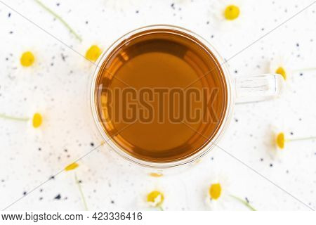 Chamomile Tea And Chamomile In Glass Mug On White Cement Table. Herbal Tea. Top View. Flat Lay