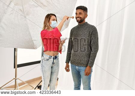 Stylist woman applying make up to handsome hispanic model at photo shoot backstage, getting ready for professional photoshoot