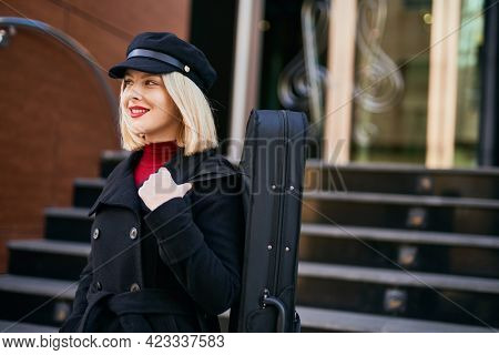Young blonde musician woman smiling happy standing at the music academy