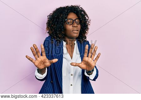 Young african american woman wearing business clothes and glasses afraid and terrified with fear expression stop gesture with hands, shouting in shock. panic concept.