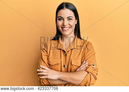 Young brunette woman wearing casual clothes happy face smiling with crossed arms looking at the camera. positive person.