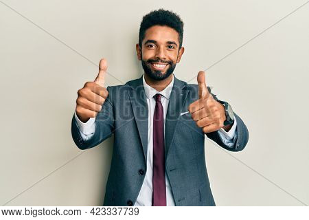 Handsome hispanic man with beard wearing business suit and tie approving doing positive gesture with hand, thumbs up smiling and happy for success. winner gesture.