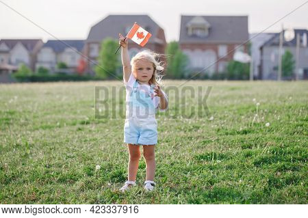Happy Canada Day. Little Blonde Caucasian Toddler Girl Holding Waving Canadian Flag. Kid Child Citiz