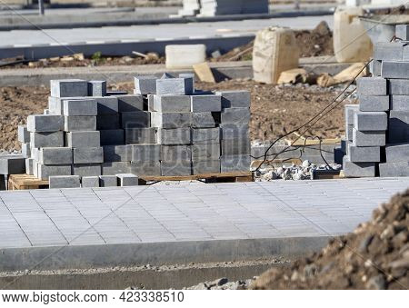 Paving Slabs Are Stacked On The Ground Next To The New Sidewalk. Building Materials For Road Constru
