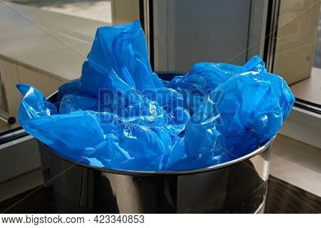 Blue Used Medical Shoe Covers In Trash. The Concept Of Hygiene And Protection. Used Shoe Covers, Dir
