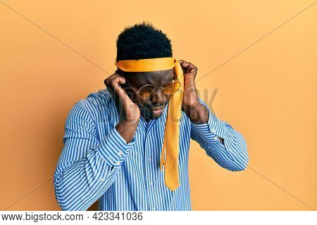 Handsome black man drunk wearing tie over head and sunglasses covering ears with fingers with annoyed expression for the noise of loud music. deaf concept.