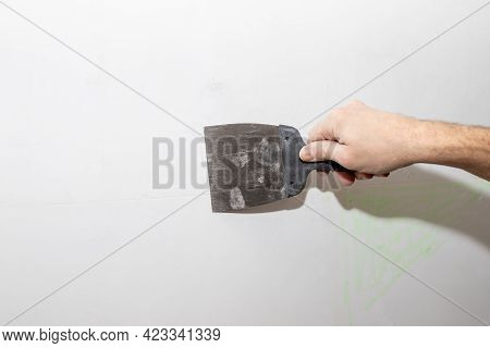 Construction Worker With Trowel Plastering A Wall.working Tool, Spatula In Hand On A Light Backgroun