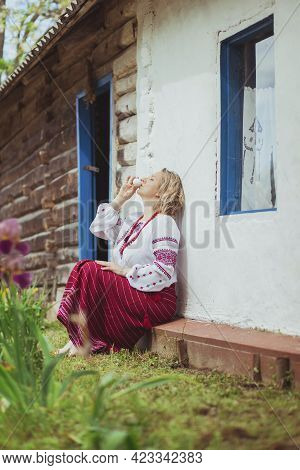 Beautiful Peasant Woman In Embroidered Clothes Drinks A Raw Chicken Egg Near The Hut