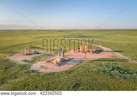oil extraction facility with a pumpjack and tanks in a green prairie, Pawnee National Grassland in Colorado in late spring - aerial view
