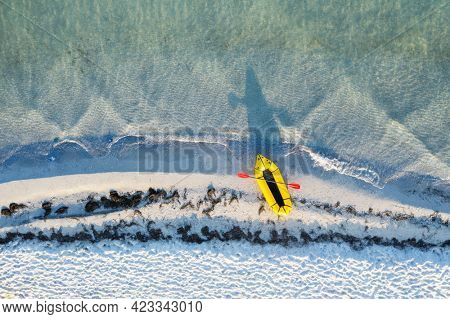 Yellow packraft rubber boat with red padle and turquoise water waves from top view. Beach with yellow sand glowing by sunlight. Travel summer vacations seascape background from drone