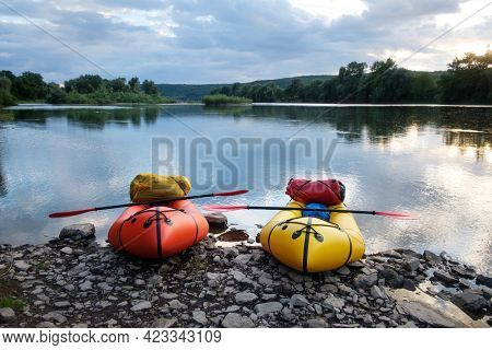 Orange and yellow packrafts rubber boats with padles ready for adventures on a sunrise river. Packrafting. Active lifestile concept