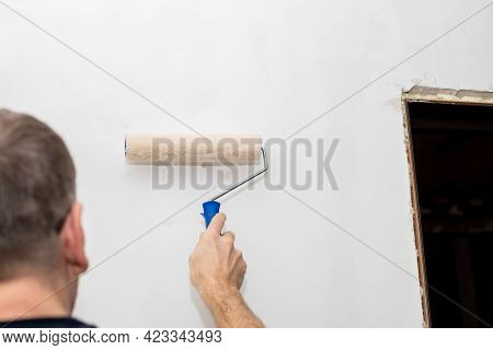 Picture Of A Hand Painting The Wall With Roller.worker Painting Wall With Paint Roller. Renovating W