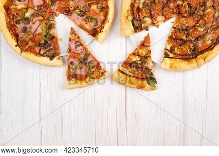 Two Different Delicious Large Pizzas On A Light Wooden Background