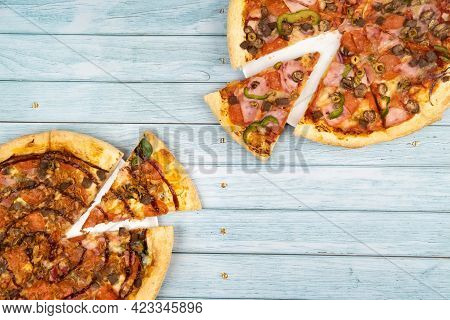 Two Different Delicious Big Pizzas On A Blue Wooden Background