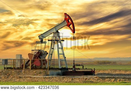 Crude Oil Pump Jack At Oilfield On Sunset Backround. Fossil Crude Output And Fuels Oil Production. O