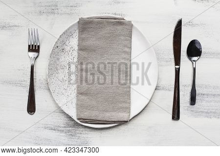 Flat Lay Of A White Spotted Plate With Napkin And Silverware Place Setting Over A Rustic Wood Table.