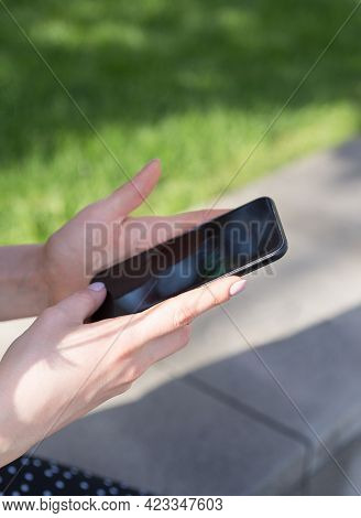 Womens Hands With A Smartphone In Their Hands On The Background Of A Green Lawn