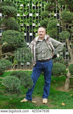 A White-haired Fifty-year-old Man In Jeans And A Shirt Stands In A City Park Near A Tree