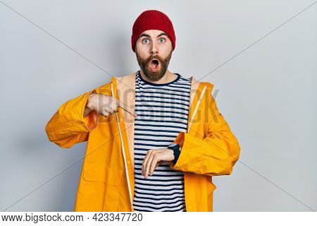 Caucasian man with beard wearing yellow raincoat in hurry pointing to watch time, impatience, upset and angry for deadline delay