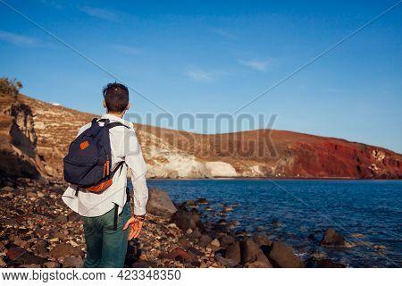Traveler Looking At Red Beach Landscape In Akrotiri, Santorini Island, Greece Admiring Sea And Mount