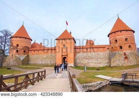 Trakai, Lithuania - February 16, 2020: Tourists On The Wooden Bridge Over Galve Lake To The Trakai O