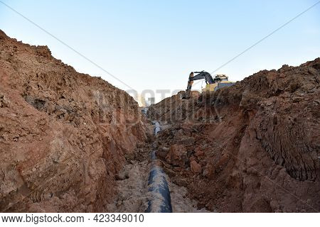 Laying Sewer Pipes. Sewage Drainage System For A Multi-story Building. Excavator Dig The Trench At A