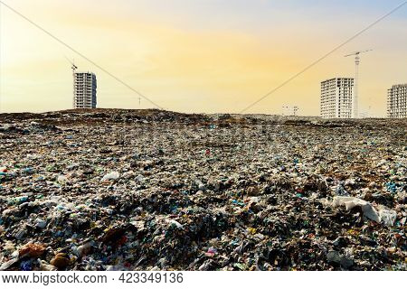 View Of The Landfill In City Against The Background Of Construction Residential Buildings. Concept O