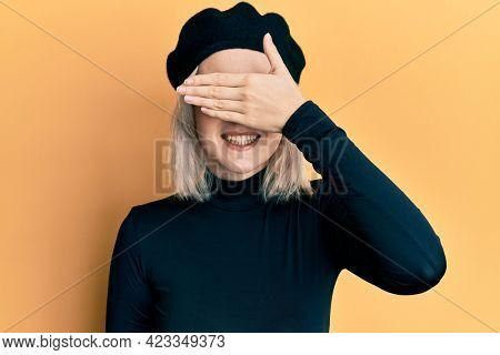 Young blonde girl wearing french look with beret smiling and laughing with hand on face covering eyes for surprise. blind concept.