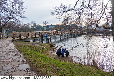 Trakai, Lithuania - February 16, 2020: A Group Of People Enjoy Sunset On A Lake. Wooden Bridge Near