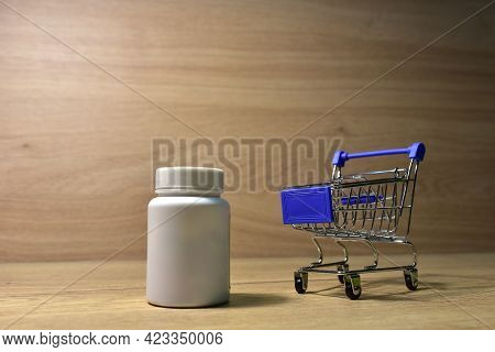 Pill Bottle In A Shopping Basket. Economy Concept Of Spending Money On Medicines And Pills. Medical