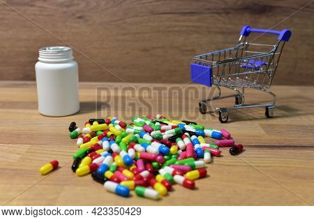 Pills At A Shopping Basket On Wood Backgrond. Economy Concept Of Spending Money On Medicines And Pil