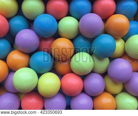 Background From Multicolored Bright Small Wooden Balls Of Blue, Yellow, Red, Lilac And Green Colors.