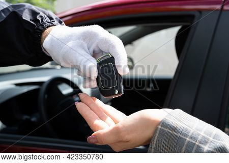 Valet Parking Giving Car Key To Young Woman