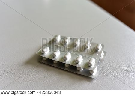 Pills In Packpage On Table. Medicine Grade Pharmaceutical Tablets. Medical Pill For Maintaining And