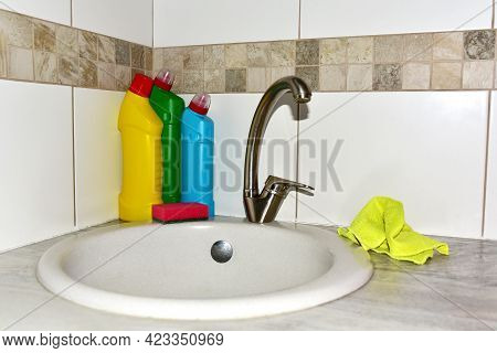Detergent Bottles Near The Kitchen Sink In Home. Detergents And Laundry Concept. Household Chemicals